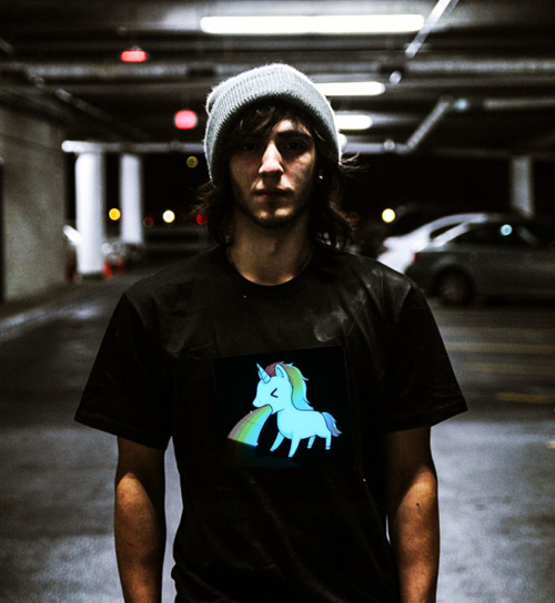 Guy in beanie wearing unicorn puking rainbow LED shirt in parking garage