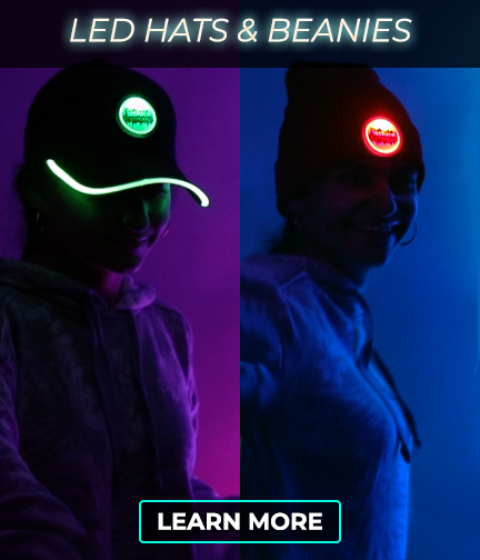 Two girls side by side, one wearing a custom LED baseball hat lighting up green and the other wearing a custom led beanie with a logo lighting up red