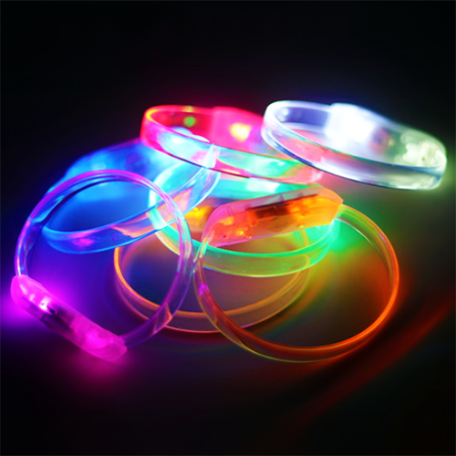 Pink, Blue, Green, Orange, yellow, Red, and white LED bracelets turned on lighting up in a pile