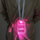 Woman in trench coat wearing LED badge on lanyard that is lighting up bright pink