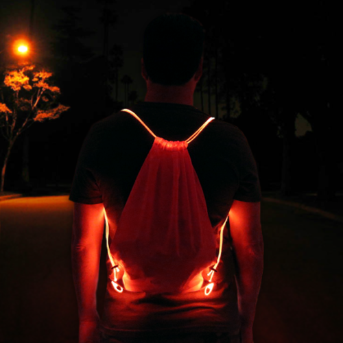 Guy wearing red LED drawstring bag in middle of street at night