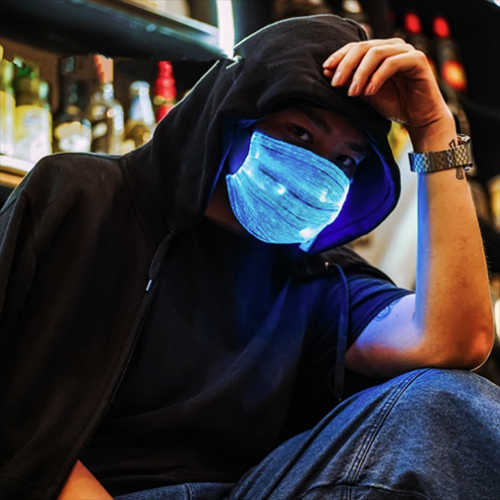 Man wearing hoodie posing on his knee while wearing a fully lit up LED mask shining bright blue